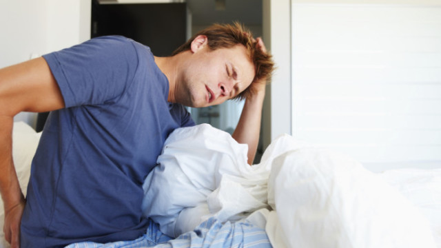 Young man waking up and discovering he has chronic back pain